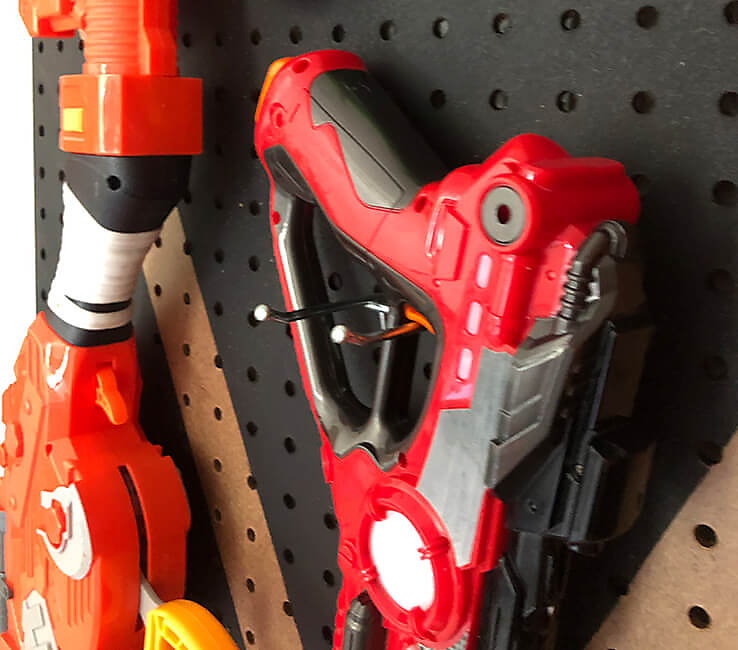 Toy Laser Tag gun hanging from pegboard